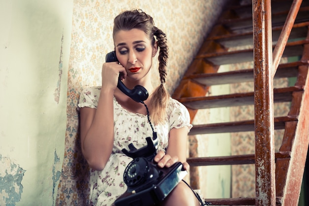 Woman sitting on the stairs and crying on the phone