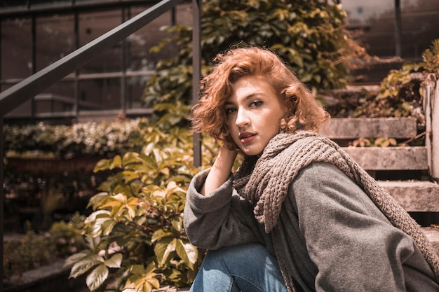 Woman sitting on steps in coat and scarf