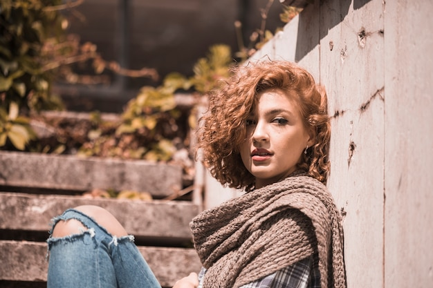 Woman sitting on steps in knitted scarf