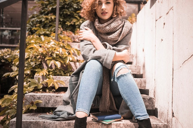 Woman sitting on steps with crossing hands