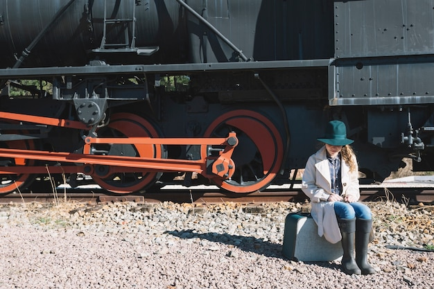 Woman sitting on suitcase at train
