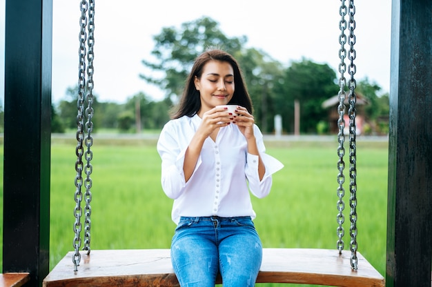 Woman sitting on a swing and holding a cup of coffee