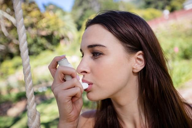 Woman sitting on swing using an asthma inhaler