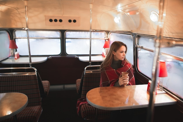 Woman sitting at the table in the bus cafe is covered with a blanket, holds a cup of coffee in her hands and looks in the window