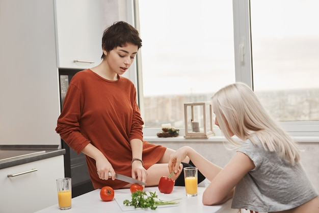 Woman sitting on table cutting tomotoes while her friend drinks orange juice
