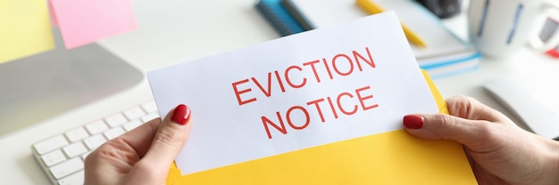 Woman sitting at table and holding eviction letter closeup