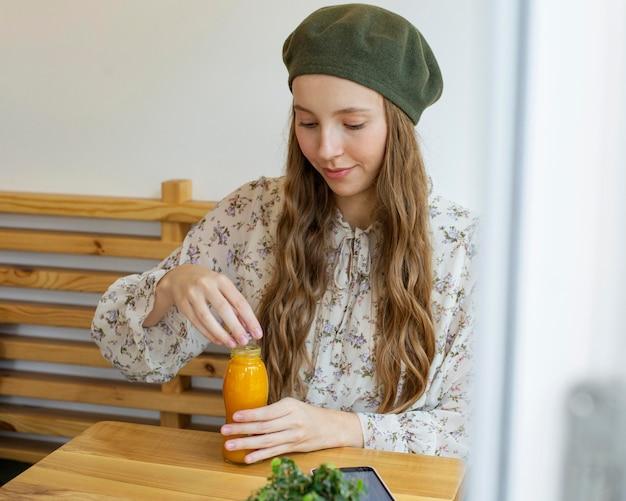Donna seduta a tavola tenendo la bottiglia di succo fresco