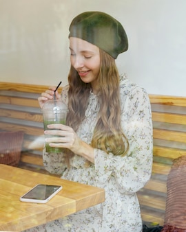 Woman sitting at table holding smoothie