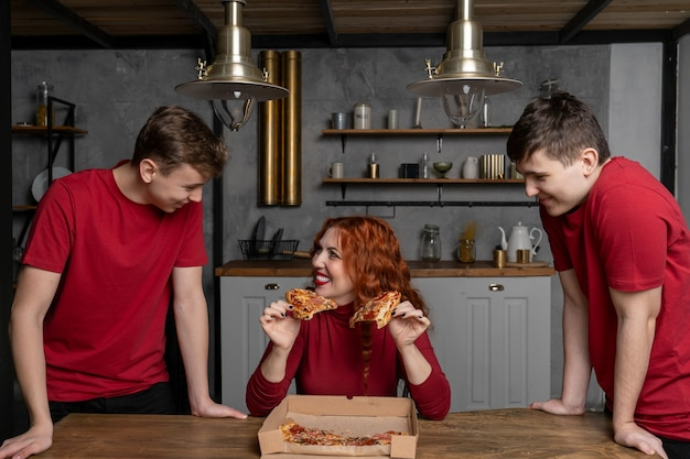 A woman sitting at the table holds two pieces of pizza in her hands and with a smile is going to share them with her sons