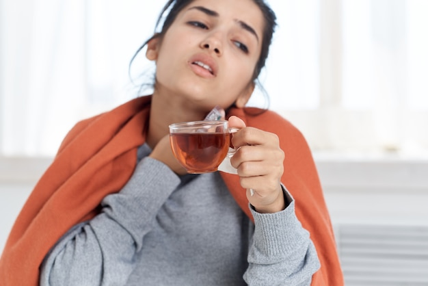 Woman sitting at the table and treatment with pills infection health problems
