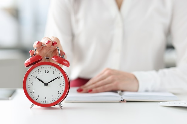 Woman sitting at table with book and clicking on alarm clock