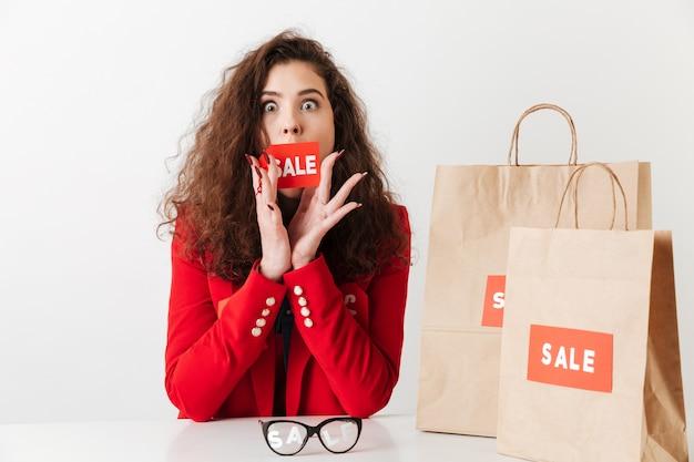 Donna che si siede al tavolo con i sacchetti della spesa di carta