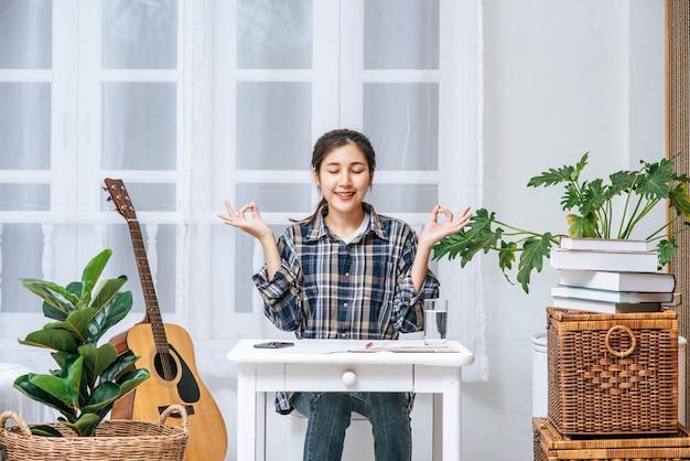 Una donna seduta al tavolo che lavora al tavolo e che fa un segno con una mano ok