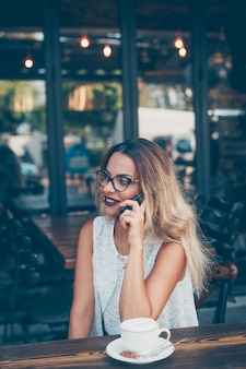 Woman sitting and talking on the phone in cafe terrace in white textured shirt during daytime