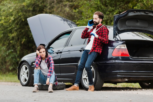 Woman sitting on tire and man talking on phone