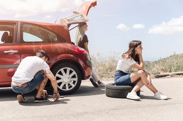 Woman sitting on tire near the man changing the car wheel on road