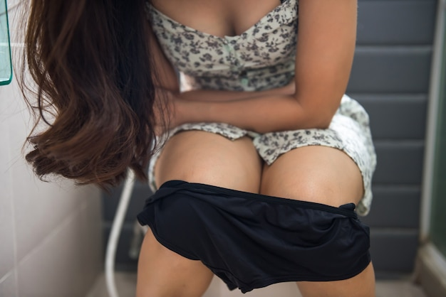Woman sitting on toilet bathroom and hold her painful stomach due to bad stomachache, diarrhea, constipation, or menstruation period. healthcare and medical concept. focus at panties.