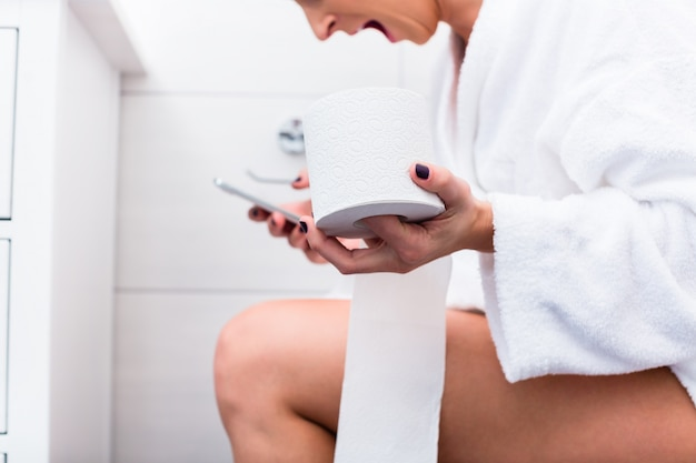 Woman sitting on toilet writing text message on cell phone