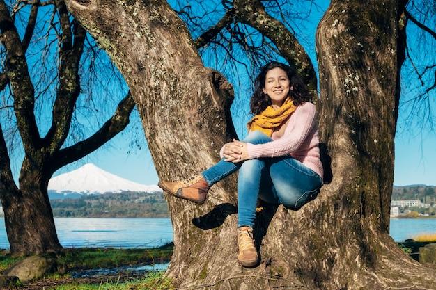笑顔の木の下に座っている女性