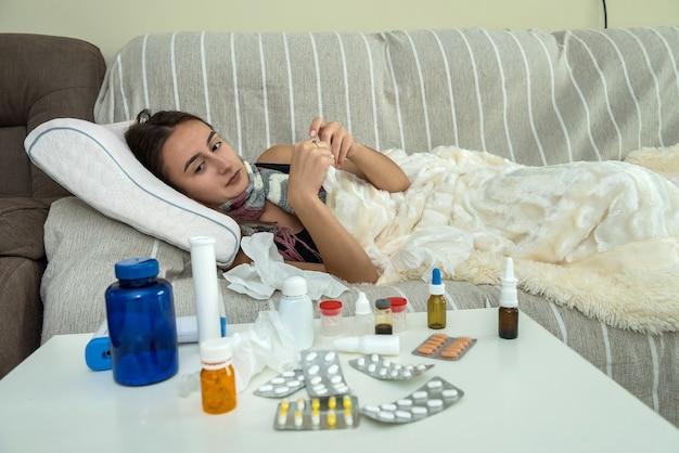ベッドの毛布の下に座っている女性は、季節性インフルエンザまたはcovid19に感染しています。在宅医療の概念
