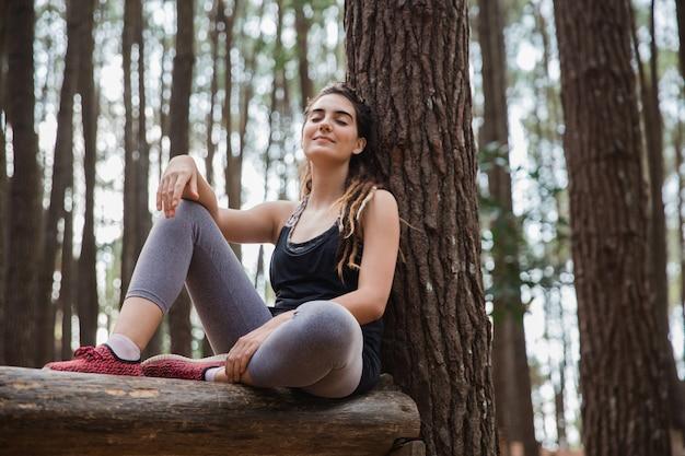 Женщина сидит под деревом