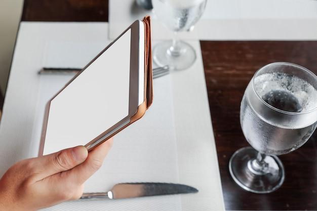 Женщина, сидящая с помощью планшета на обеденном столе в ресторане