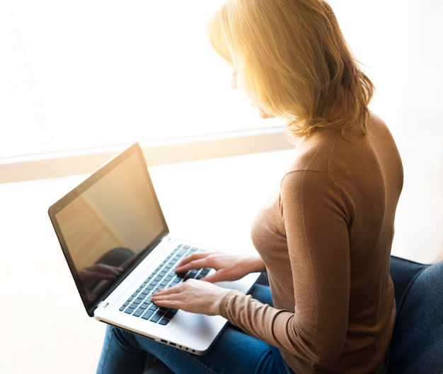 Woman sitting and using laptop