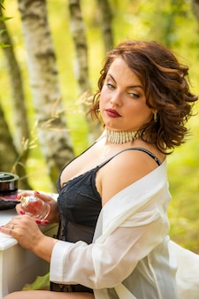 Woman sitting and using perfume in the forest
