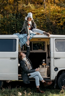 Woman sitting on a van and talking with her boyfriend