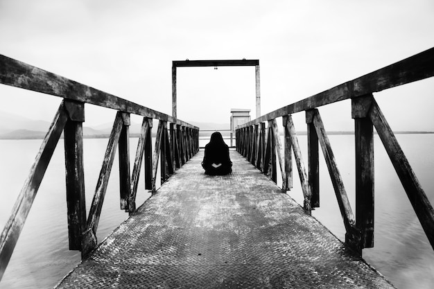 Woman sitting at water level gate, horror scene in white tone