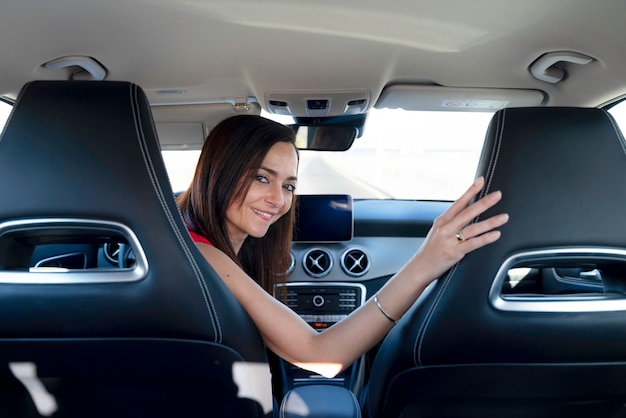 Woman sitting behind the wheel of a car looks back smiling.