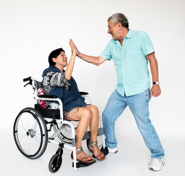 Woman sitting on wheelchair and man standing for photoshoot