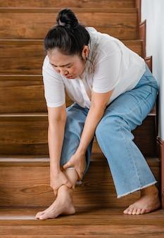 Женщина, сидящая, когда не может ходить по лестнице, останавливается, затем держится за ноги для поддержки и отдыха, чувствуя покалывание. понятие синдрома гийена-барре и болезни онемения ног или побочного эффекта вакцины.