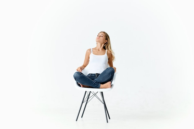 Woman sitting on white chair with bent legs emotions lifestyle light background