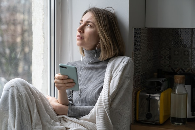 Woman sitting on windowsill, looking at window at home, holding phone and listening to music