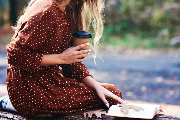 一杯のコーヒーと屋外で本と一緒に座っている女性