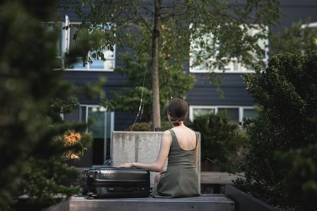 Женщина сидит с чемоданом в парке