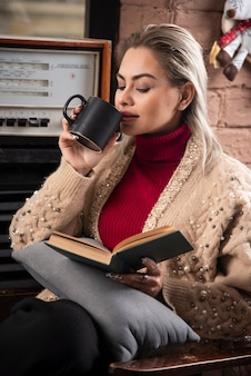 A woman sitting with a book and drinking coffee
