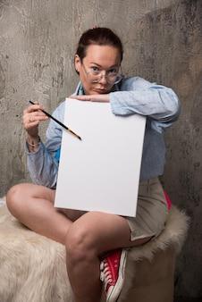 Donna seduta con tela e pennello su marmo. foto di alta qualità