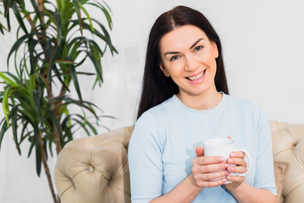 Woman sitting with coffee cup on couch