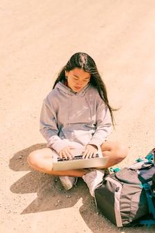도로에 다리를 건너 앉아 노트북에서 일하는 여자