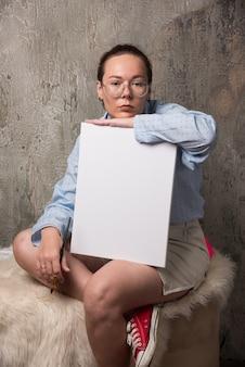 빈 흰색 캔버스와 대리석 배경 브러시와 함께 앉아 여자.
