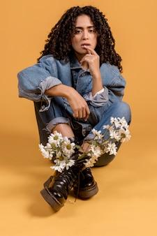 Женщина сидит с цветами в сапогах