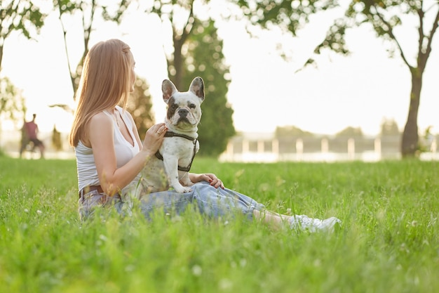 Woman sitting with french bulldog on grass