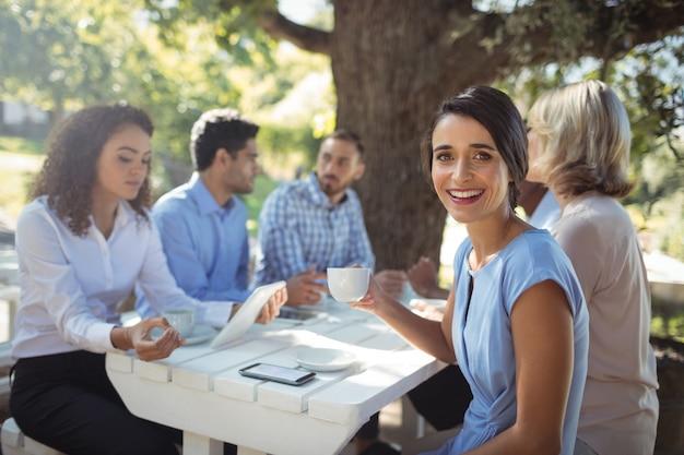 Женщина, сидящая с друзьями в ресторане на открытом воздухе