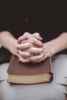 彼女の膝の上の本に一緒に手で座っている女性