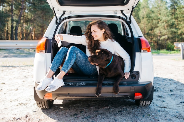 Woman sitting with her dog in open trunk