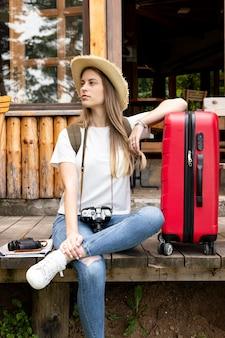 Женщина сидит с багажом и смотрит в сторону