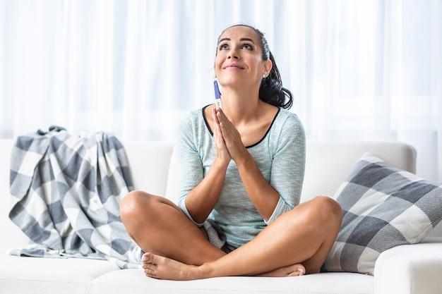 소파에 다리를 꼬고 앉아 있는 여성이 임신 테스트기를 들고 기도합니다.