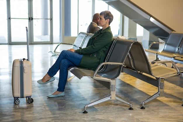 Donna seduta con i bagagli nell'area di attesa